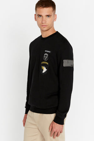 Side view of men wearing a black long sleeve crew neck sweater with patches on left chest and patch on left sleeve