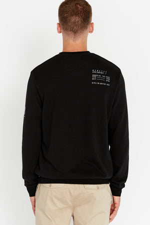 Back view of men wearing a black long sleeve crew neck sweater with text near right shoulder on the back