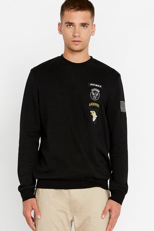 Men wearing a black long sleeve crew neck sweater with patches on left chest and patch on left sleeve