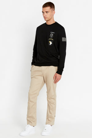 Side full view of men wearing a black long sleeve crew neck sweater with patches on left chest and patch on left sleeve and light beige pants