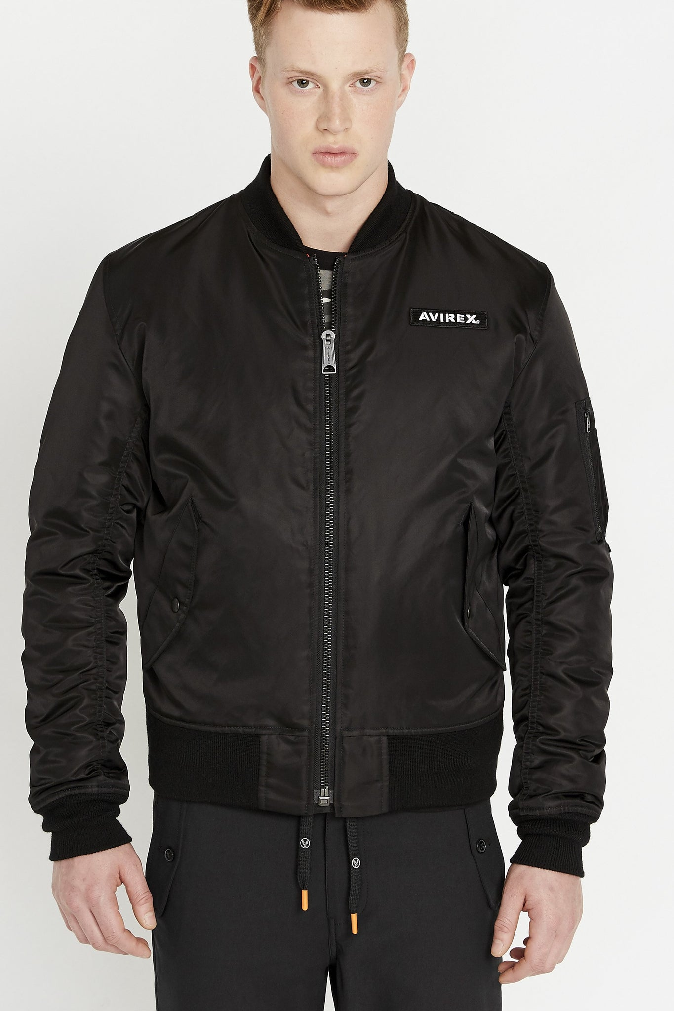 Front view of men wearing a fully zipped black original aviation bomber nylon jacket with Iconic utility pocket on sleeve and two side pockets