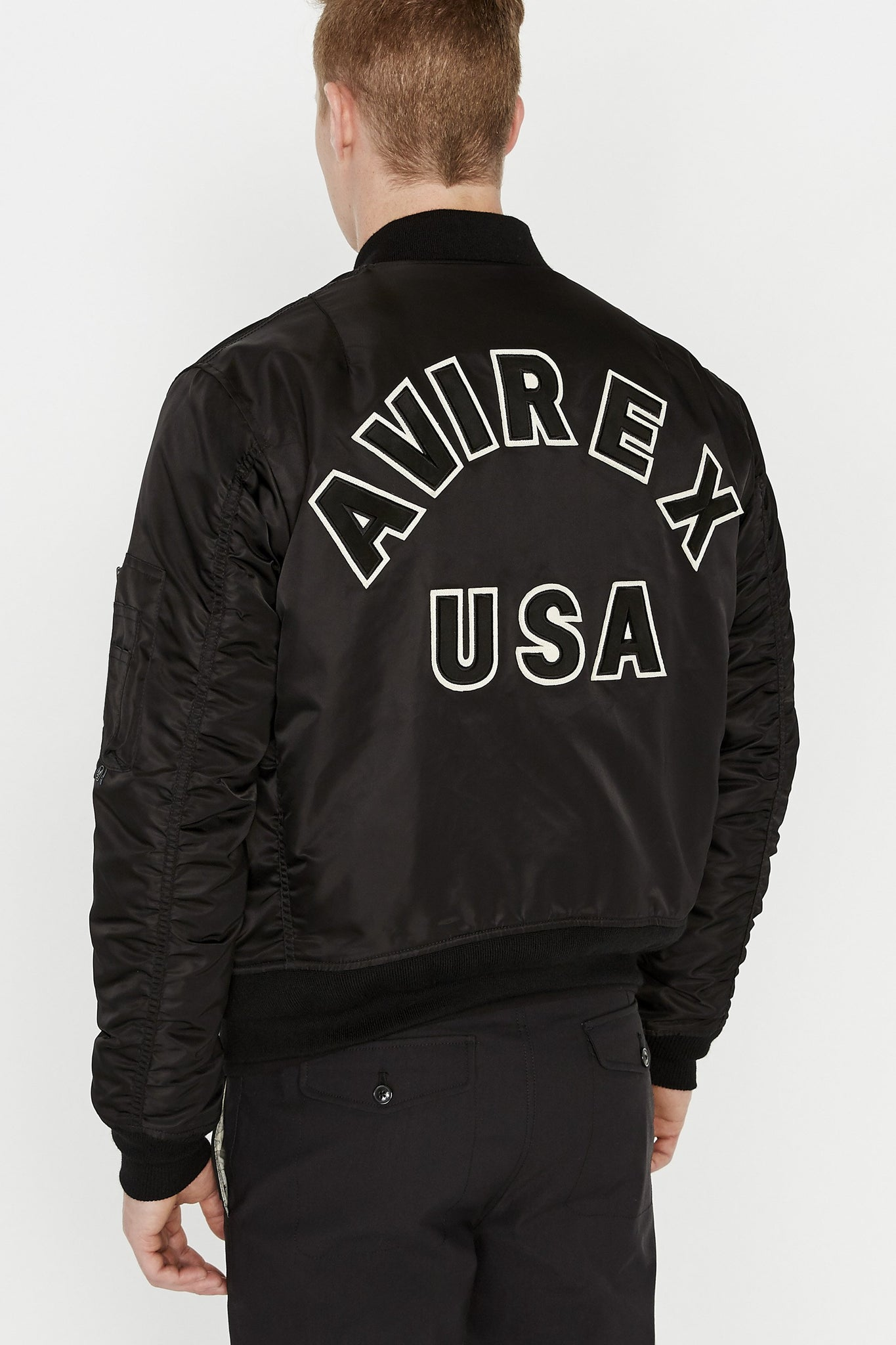 Back view of men wearing a black original aviation bomber nylon jacket with bold black text lettering Avirex USA