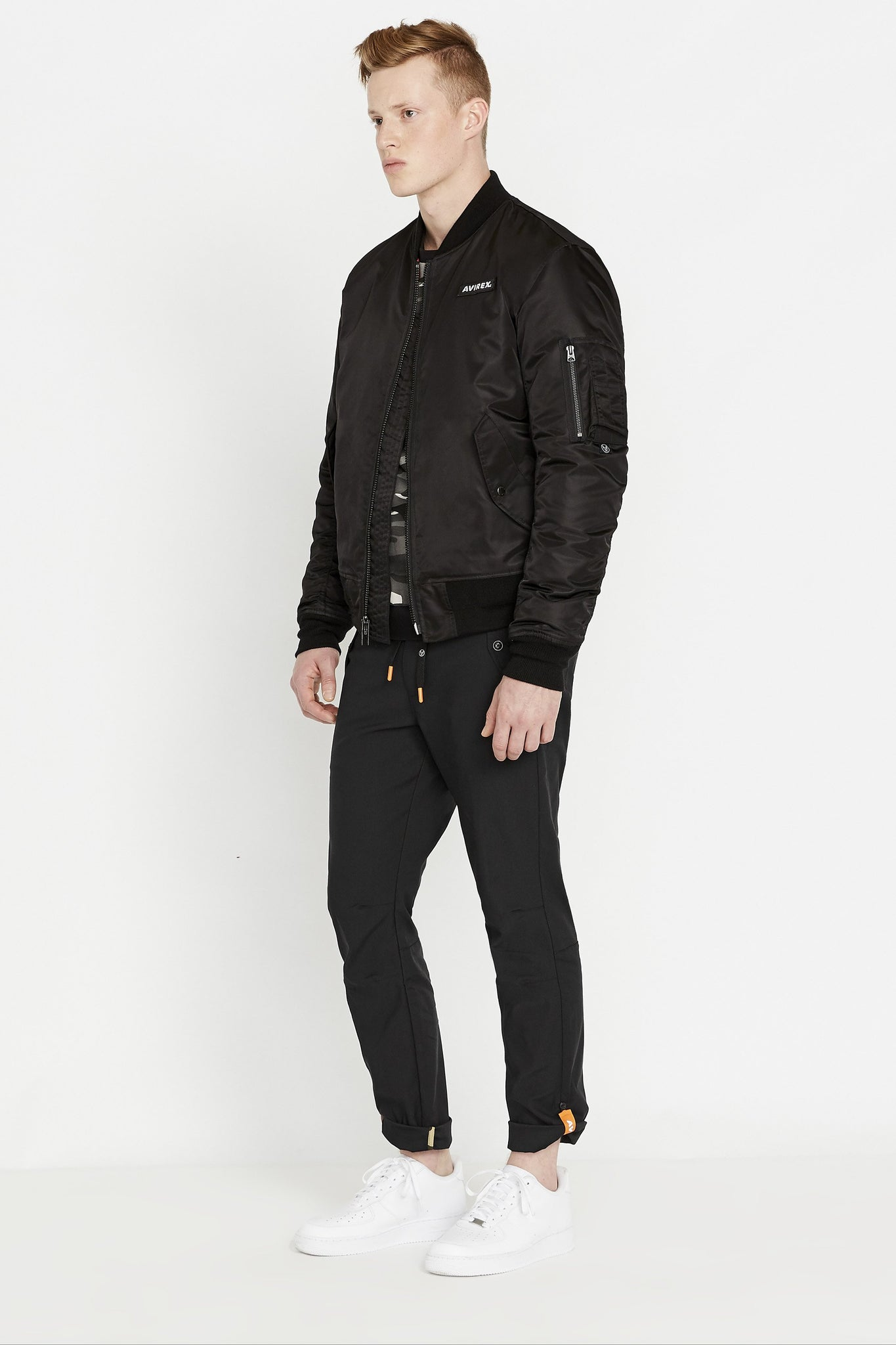 Side full view of men wearing an open black original aviation bomber nylon jacket with Iconic utility pocket on sleeve and two side pockets and black pants