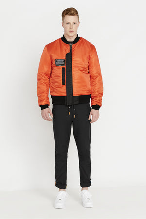 Full view of men wearing a fully zipped reversed orange aviation bomber nylon jacket with patch on right chest and two pockets and black pants