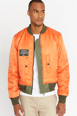 Front view of men wearing an open reversed orange aviation bomber nylon jacket with patch on right chest and two pockets