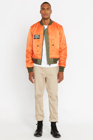Full view of men wearing an open reversed orange aviation bomber nylon jacket with patch on right chest and two pockets and light beige pants