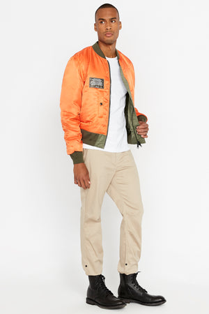 Side full view of men wearing an open reversed orange aviation bomber nylon jacket with patch on right chest and two pockets and light beige pants
