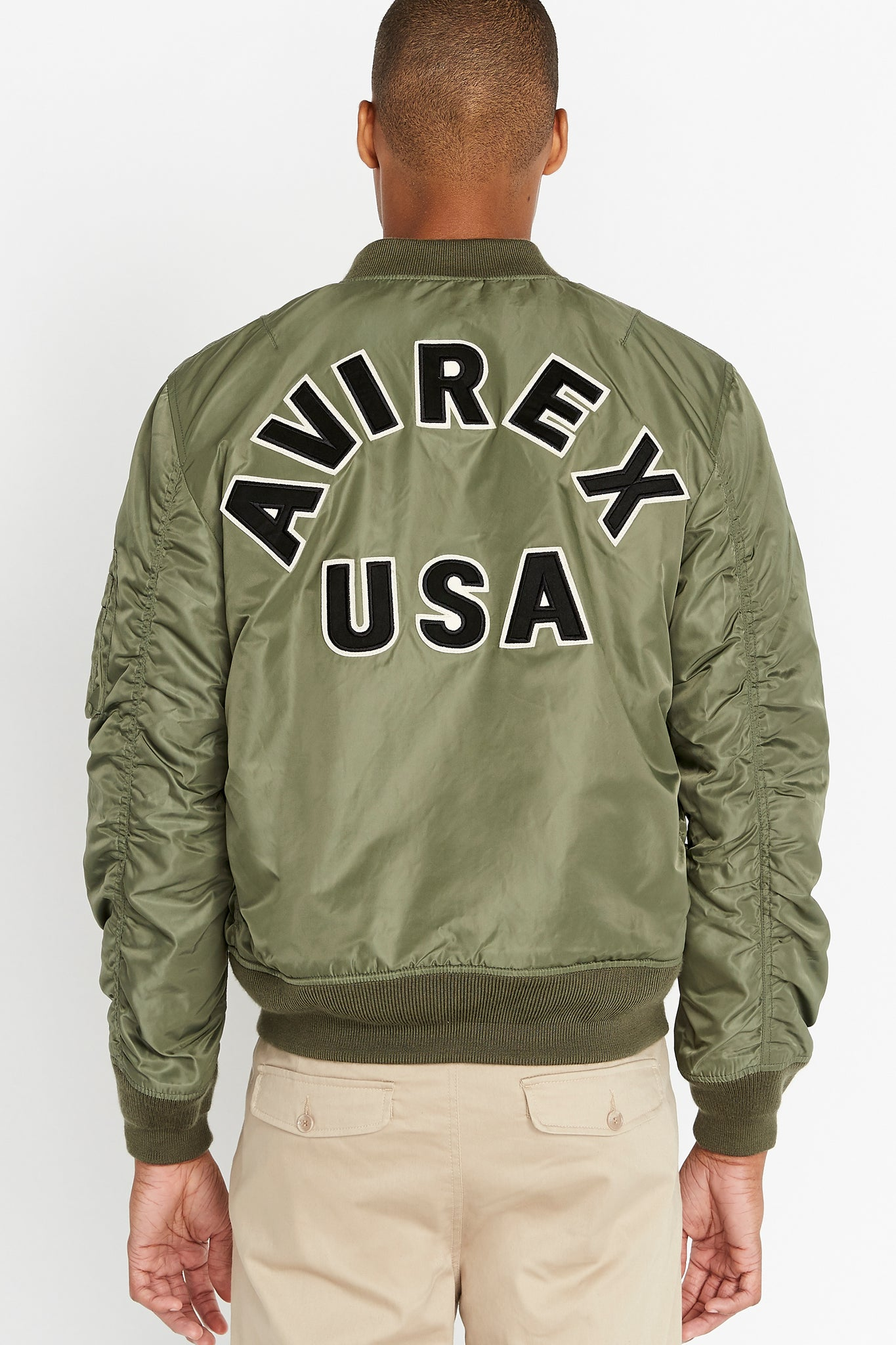 Back view of men wearing an olive original aviation bomber nylon jacket with bold black text lettering Avirex USA