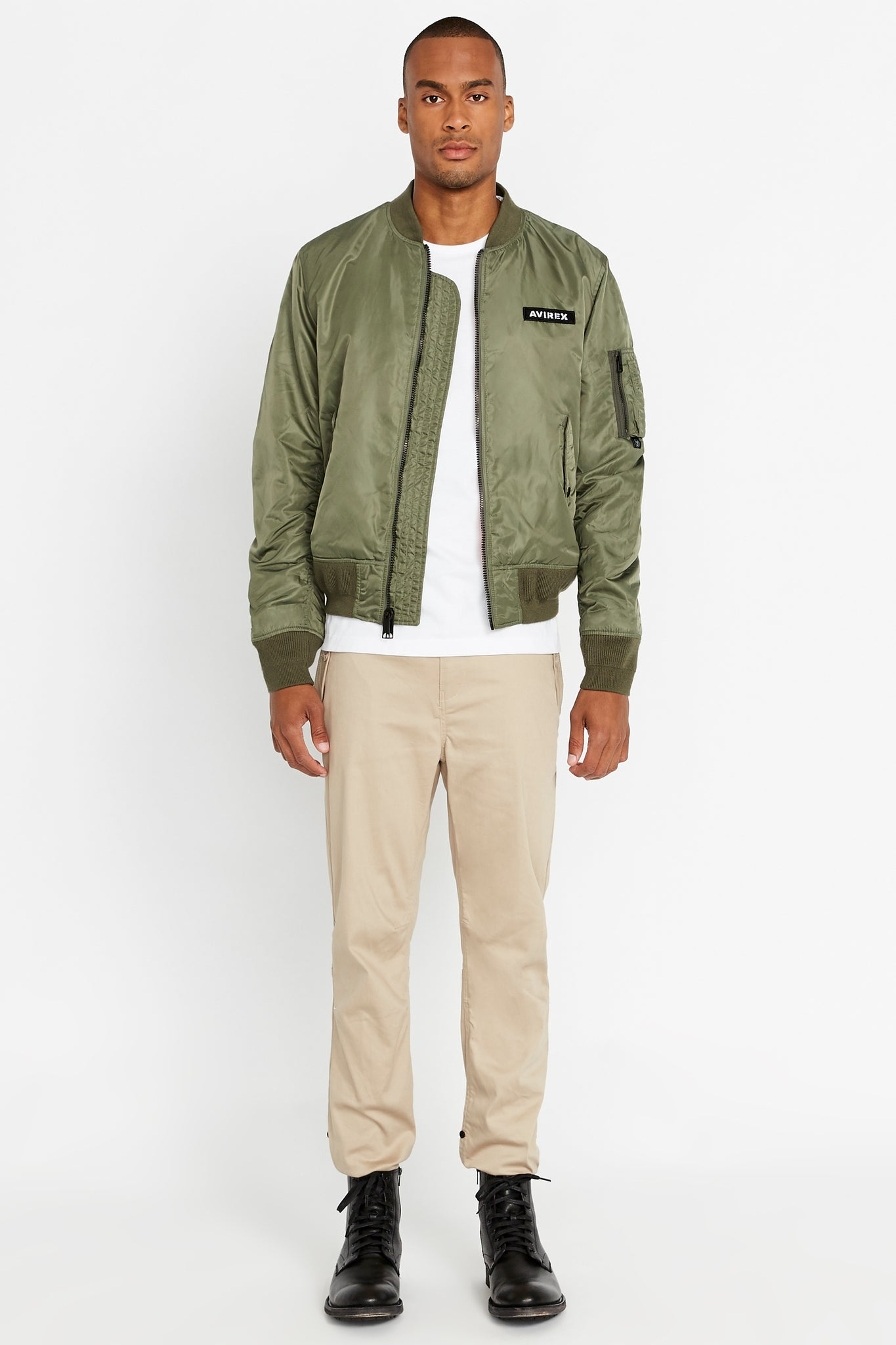 Full view of men wearing an open olive original aviation bomber nylon jacket with Iconic utility pocket on sleeve and two side pockets and light beige pants
