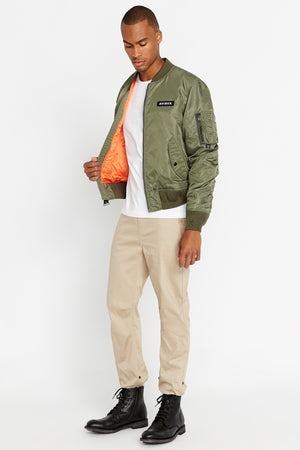 Side full view of men wearing an open olive original aviation bomber nylon jacket with Iconic utility pocket on sleeve and two side pockets and light beige pants