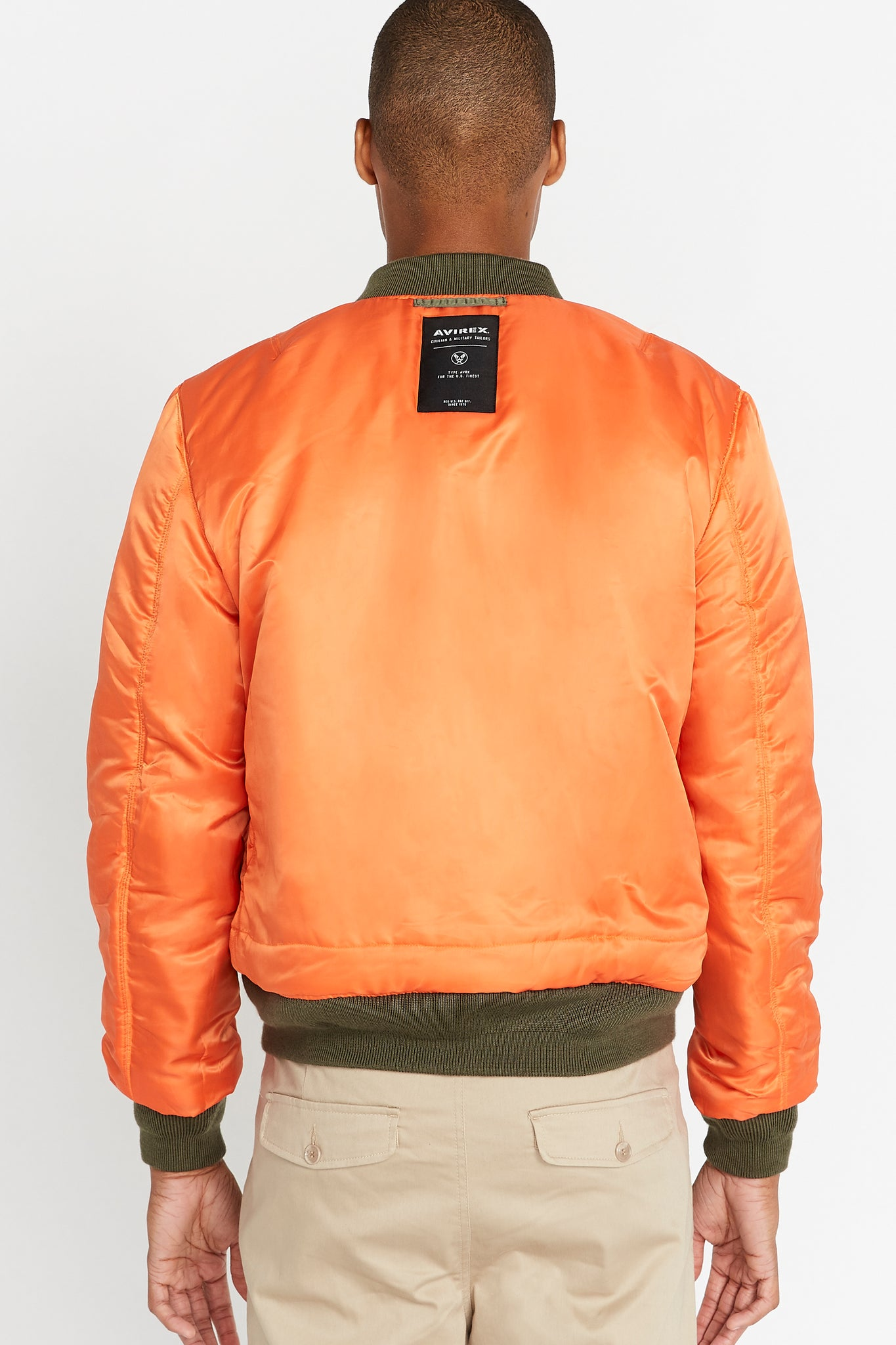 Back view of men wearing a reversed orange aviation bomber nylon jacket with patch under collar