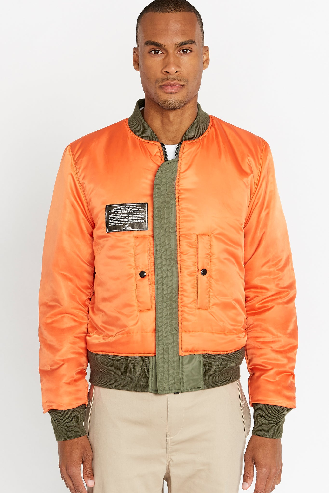 Front view of men wearing a fully zipped reversed orange aviation bomber nylon jacket with patch on right chest and two pockets