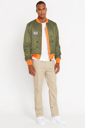 Full view of men wearing an open reversed olive aviation bomber nylon jacket with patch on right chest and two pockets and light beige pants