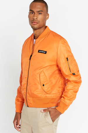 Side view of men wearing a fully zipped orange original aviation bomber nylon jacket with Iconic utility pocket on sleeve and two side pockets
