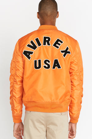 Back view of men wearing an orange original aviation bomber nylon jacket with bold black text lettering Avirex USA