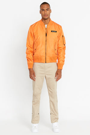 Full view of men wearing a fully zipped orange original aviation bomber nylon jacket with Iconic utility pocket on sleeve and two side pockets and light beige pants