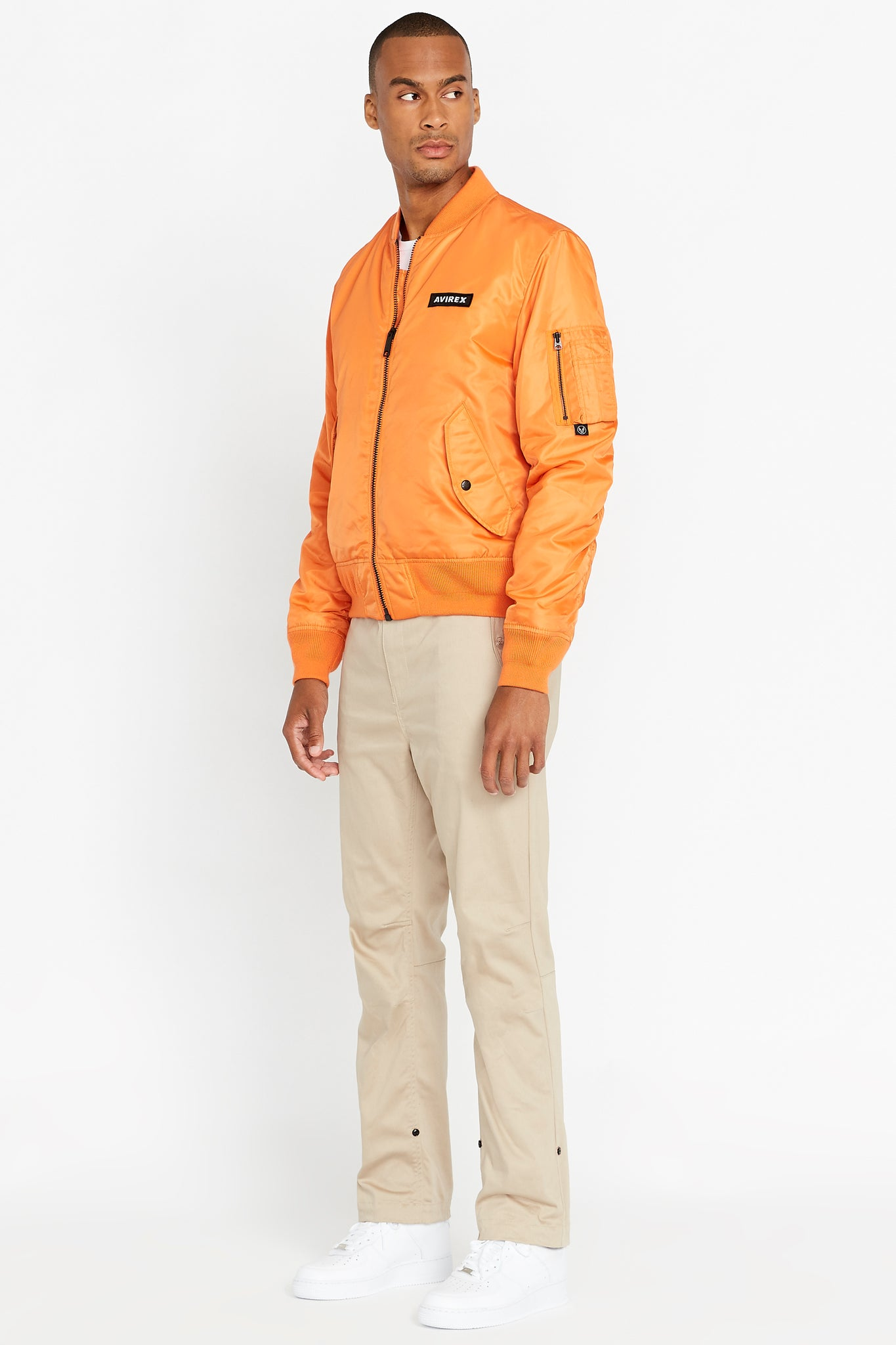 Side full view of men wearing a fully zipped orange original aviation bomber nylon jacket with Iconic utility pocket on sleeve and two side pockets and light beige pants