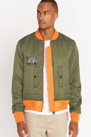 Front view of men wearing an open reversed olive aviation bomber nylon jacket with patch on right chest and two pockets