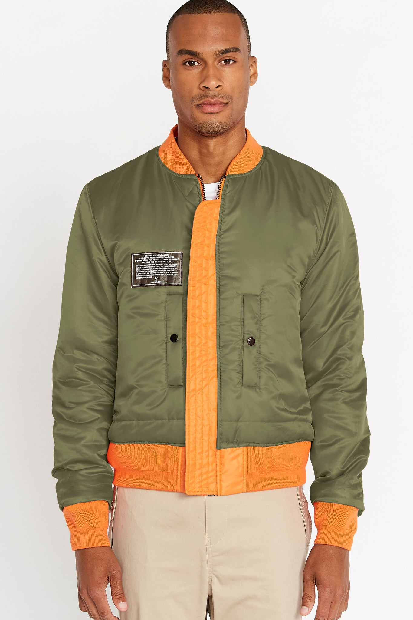 Front view of men wearing a fully zipped reversed olive aviation bomber nylon jacket with patch on right chest and two pockets
