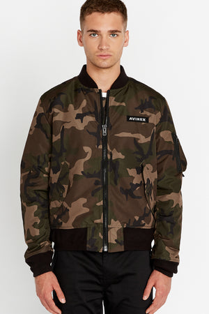 Front view of men wearing a fully zipped camo printed bomber jacket with two side pockets and one utility pocket on the left sleeve, Avirex logo patch on the chest
