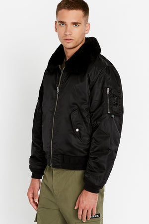 Side view of men wearing a fully zipped black bomber jacket with a sherpa-lined collar and two side flap pockets and one utility pocket on the left sleeve
