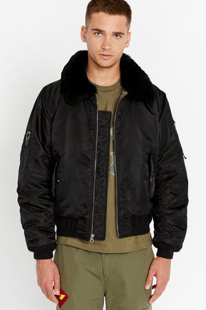 Front view of men wearing an open black bomber jacket with a sherpa-lined collar and two side flap pockets and one patch on the right sleeve, one utility pocket on the left sleeve