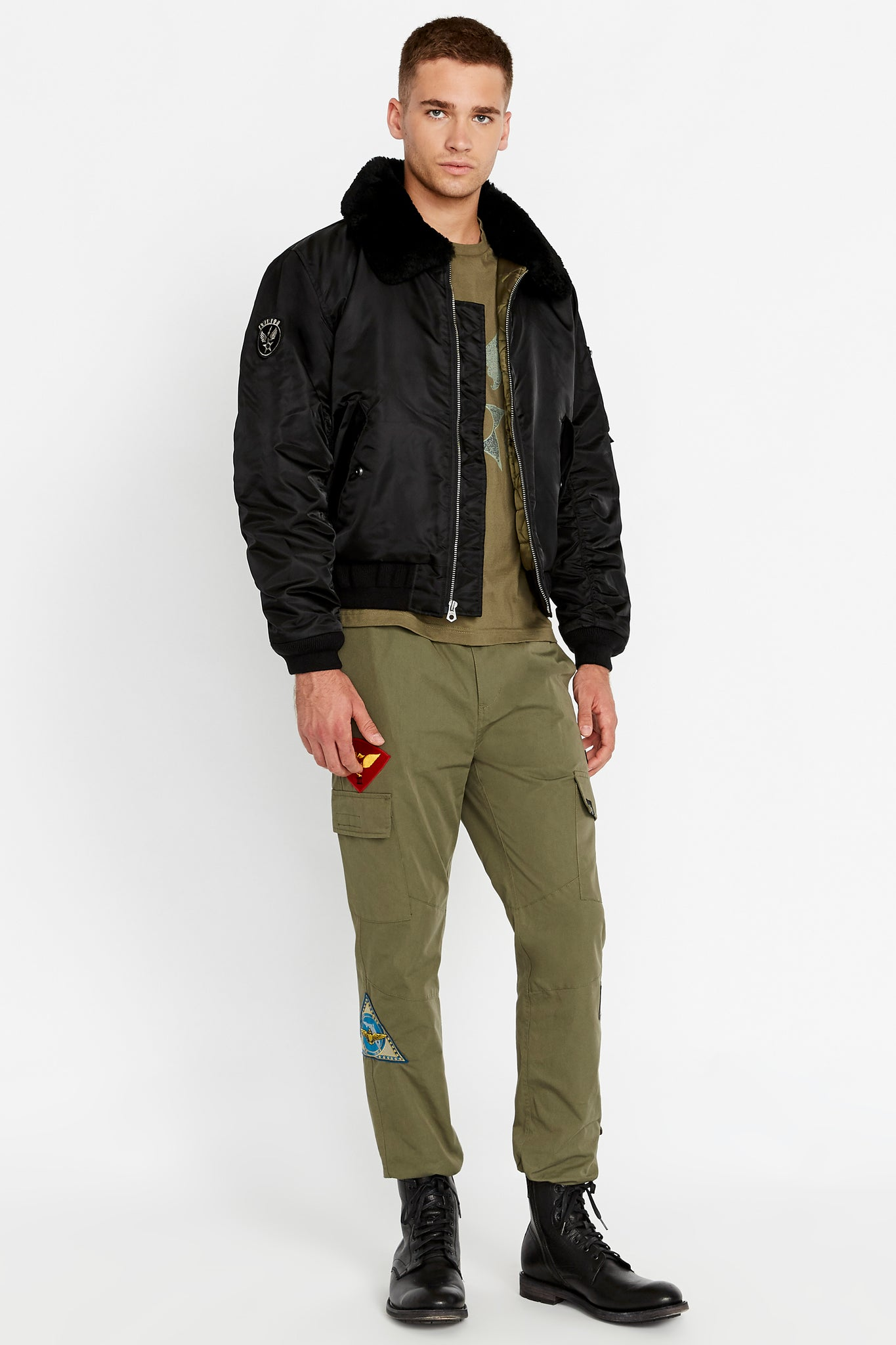 Full side view of men wearing an open black bomber jacket with a sherpa-lined collar and two side flap pockets and one patch on the right sleeve and olive pants