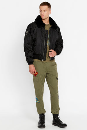Full side view of men wearing an open black bomber jacket with a sherpa-lined collar and two side flap pockets and one patch on the right sleeve and olive pants|color::Jet Black