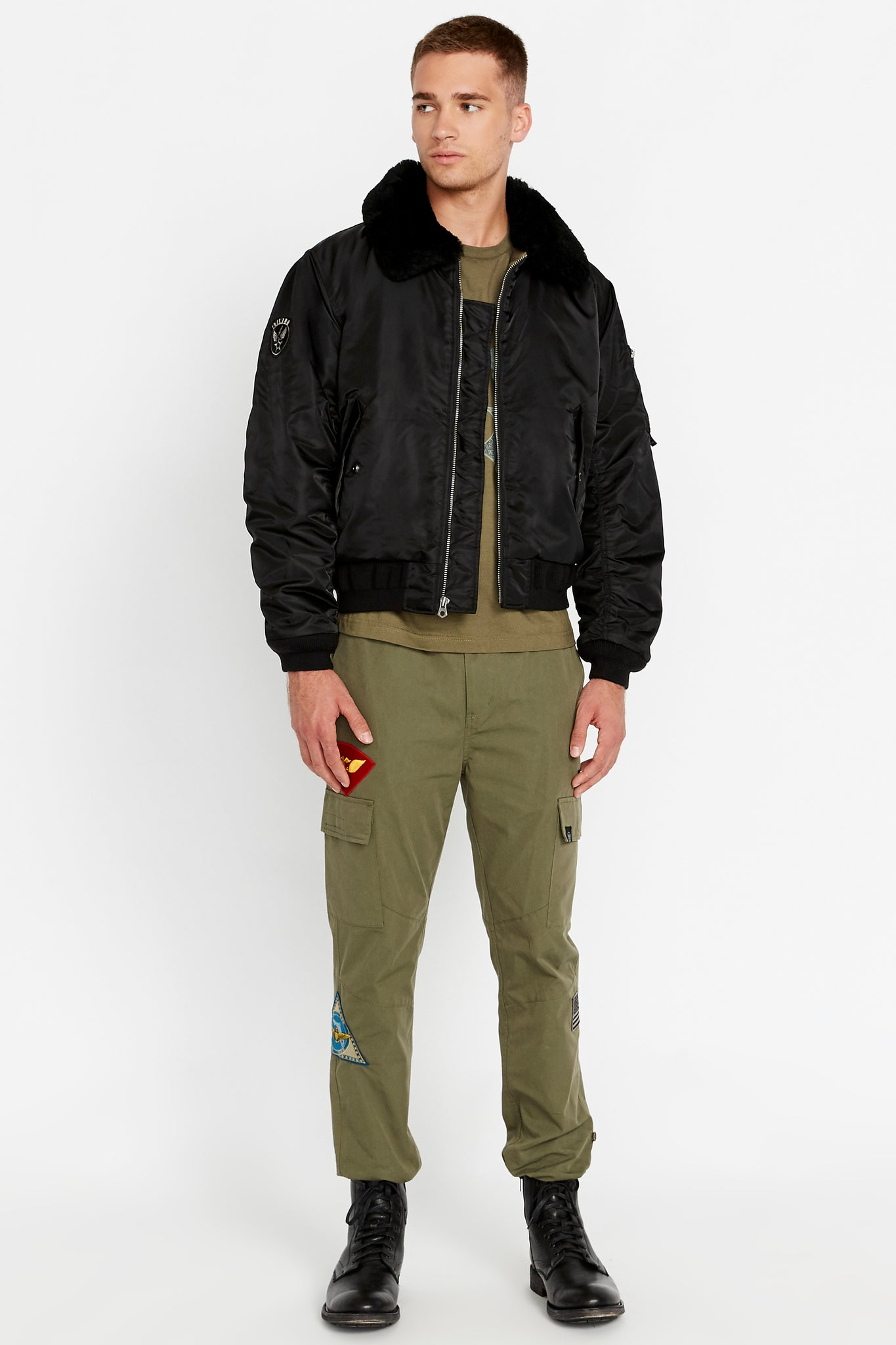Full front view of men wearing an open black bomber jacket with a sherpa-lined collar and two side flap pockets and one patch on the right sleeve, one utility pocket on the left sleeve and olive pants