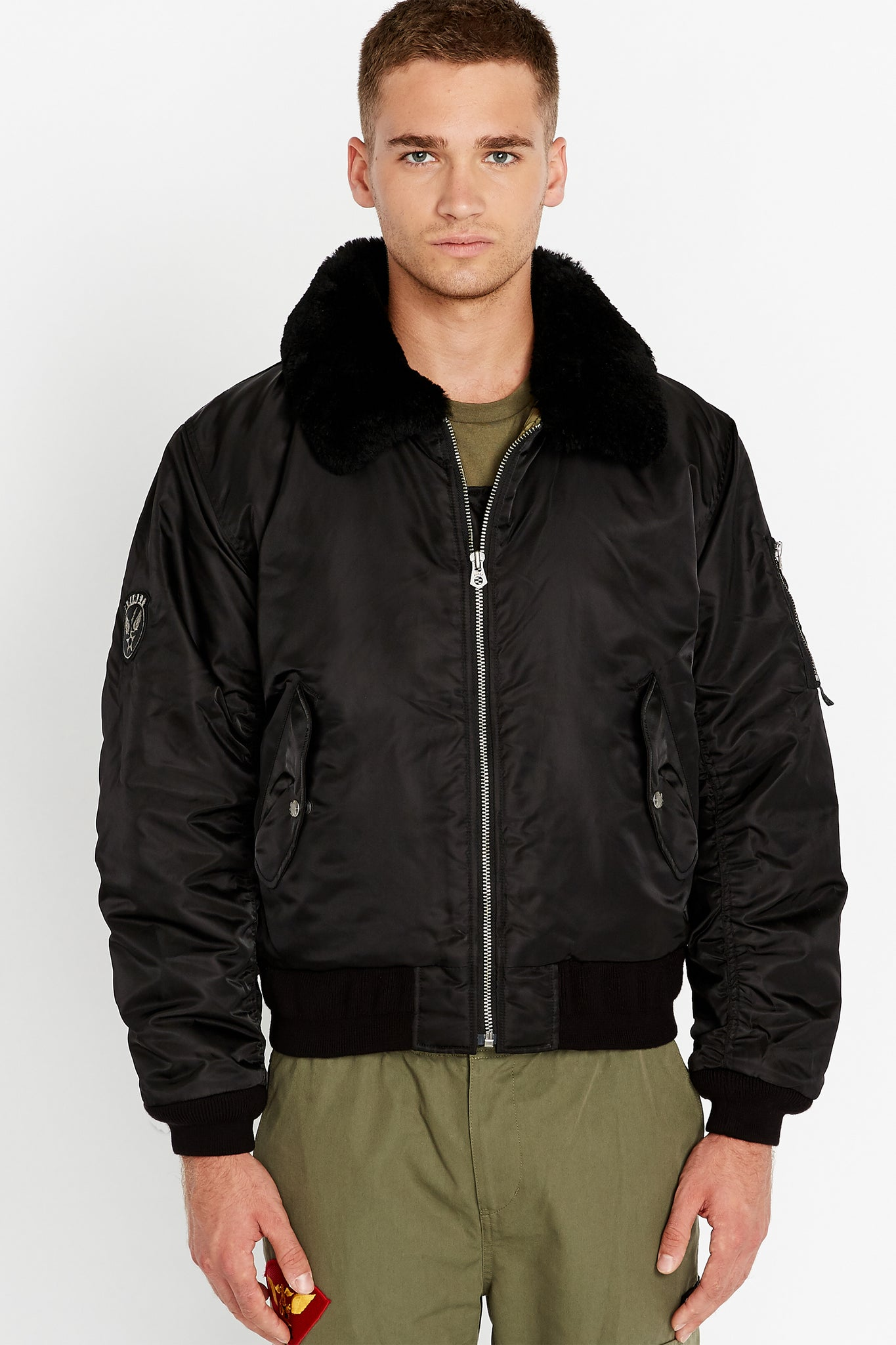 Front view of men wearing a fully zipped black bomber jacket with a sherpa-lined collar and two side flap pockets and one patch on the right sleeve, one utility pocket on the left sleeve
