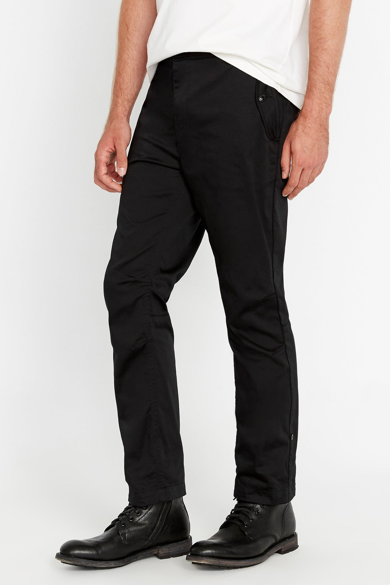 Side view of men wearing black pants with button flap pockets