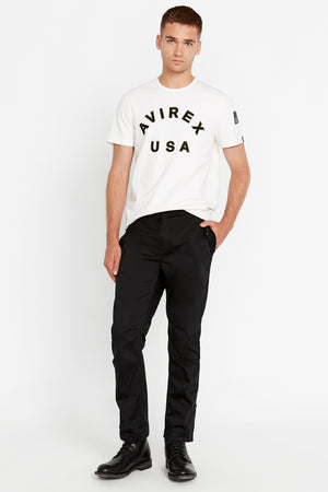 Full View of men wearing a black pants with side pockets and white short sleeve crew neck T-shirt