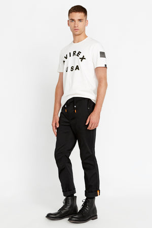 Full side view of men wearing black pants with button flap pockets, rolled up hem with reflective logo and white short sleeve crew neck T-shirt