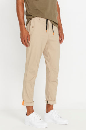 Side view of men wearing khaki pants with button flap pockets and rolled up hem with reflective logo