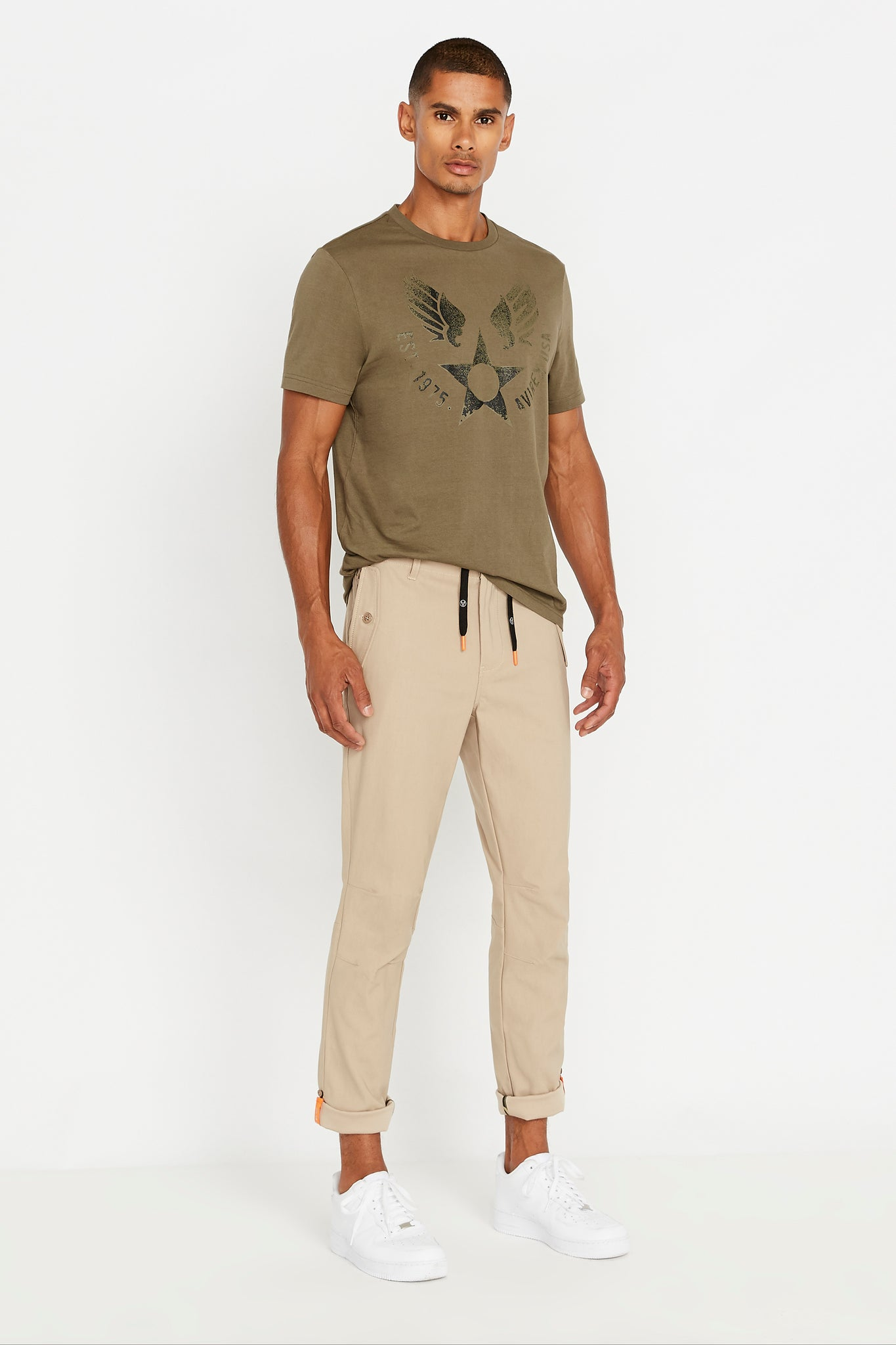 Full View of men wearing a khaki pants with side pockets and olive short sleeve crew neck T-shirt