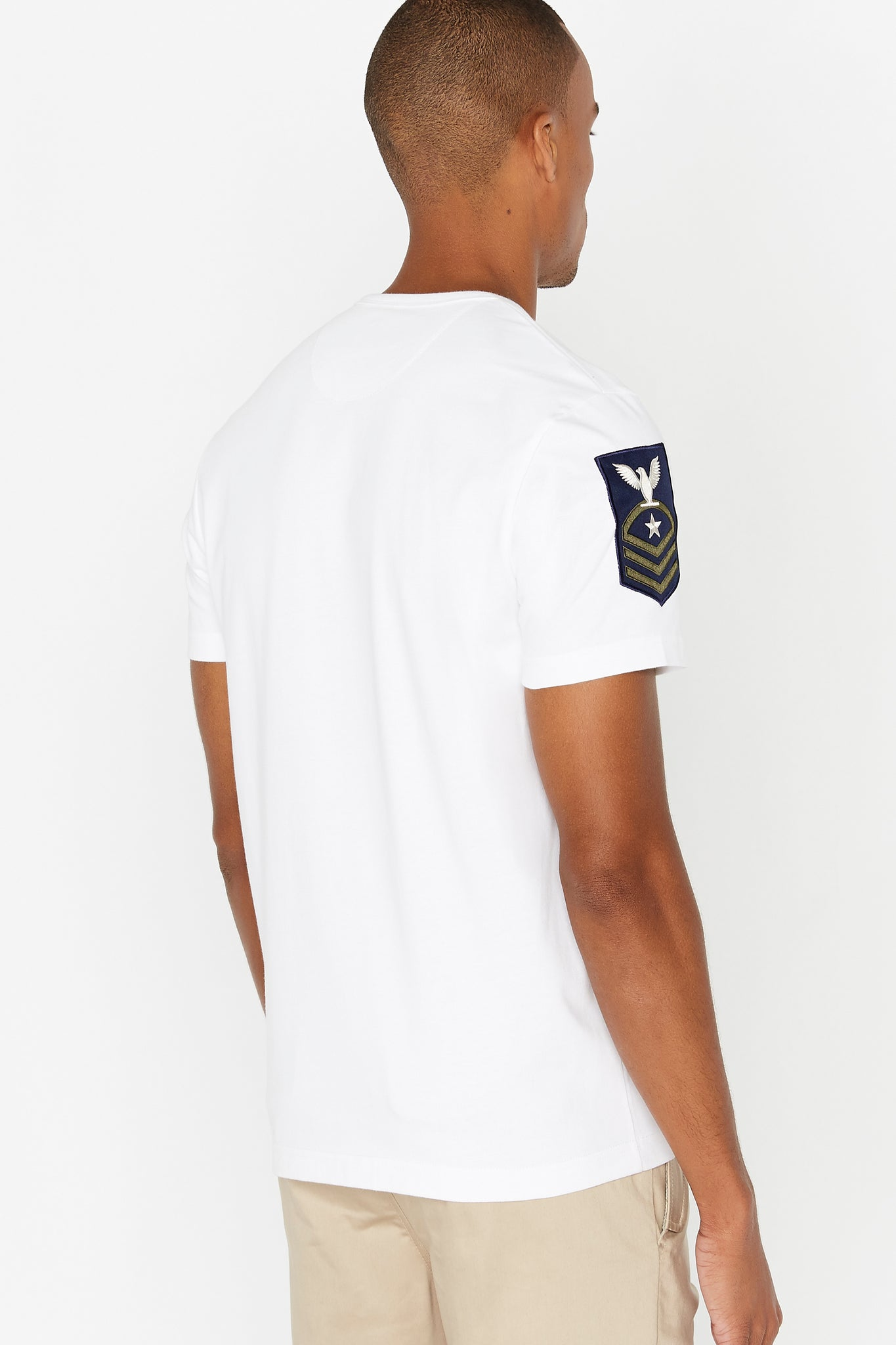 Side view of men wearing a white short sleeve crew T-shirt with a patch on right sleeve
