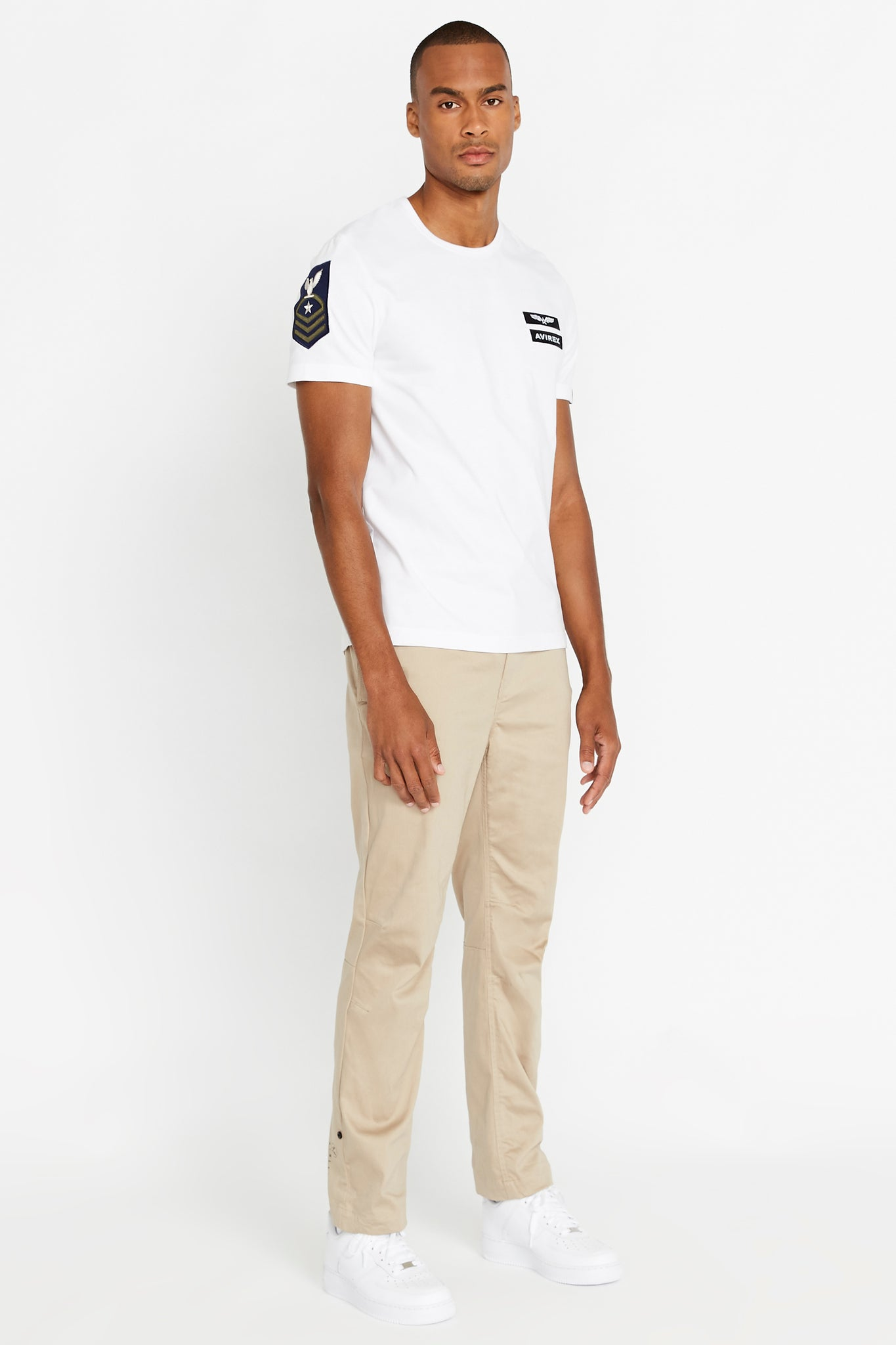 Full view of men wearing a white short sleeve crew T-shirt with Avirex logo and letters patches on left chest and light beige pants