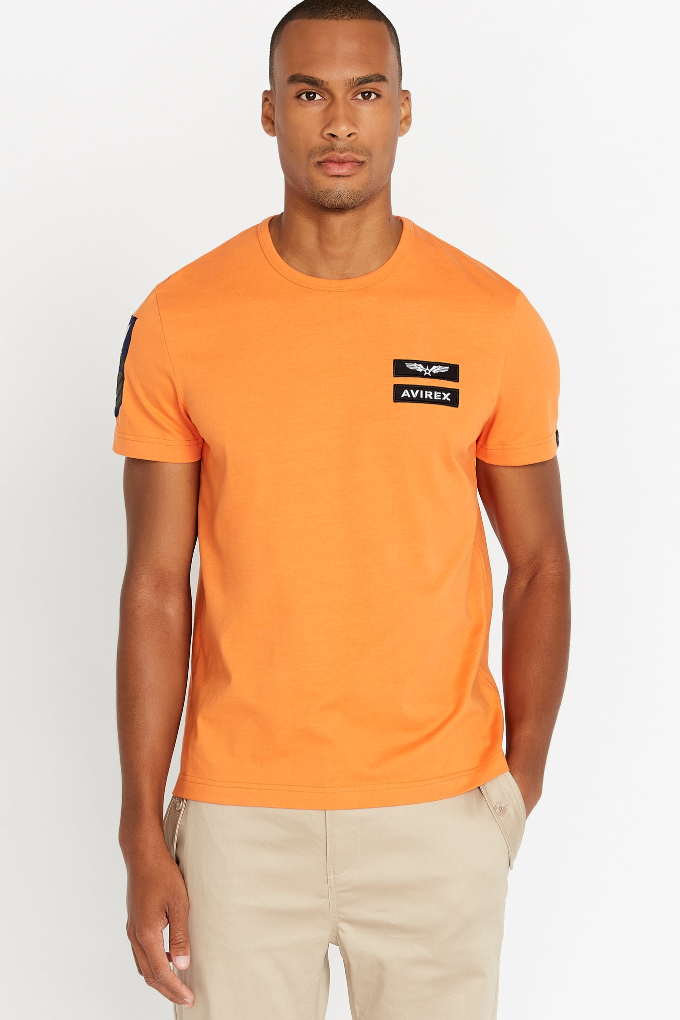 Men wearing a light orange short sleeve crew T-shirt with Avirex logo and letters patches on left chest and a patch on right sleeve
