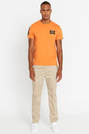 Full view of men wearing a light orange short sleeve crew T-shirt with Avirex logo and letters patches on left chest and light beige pants