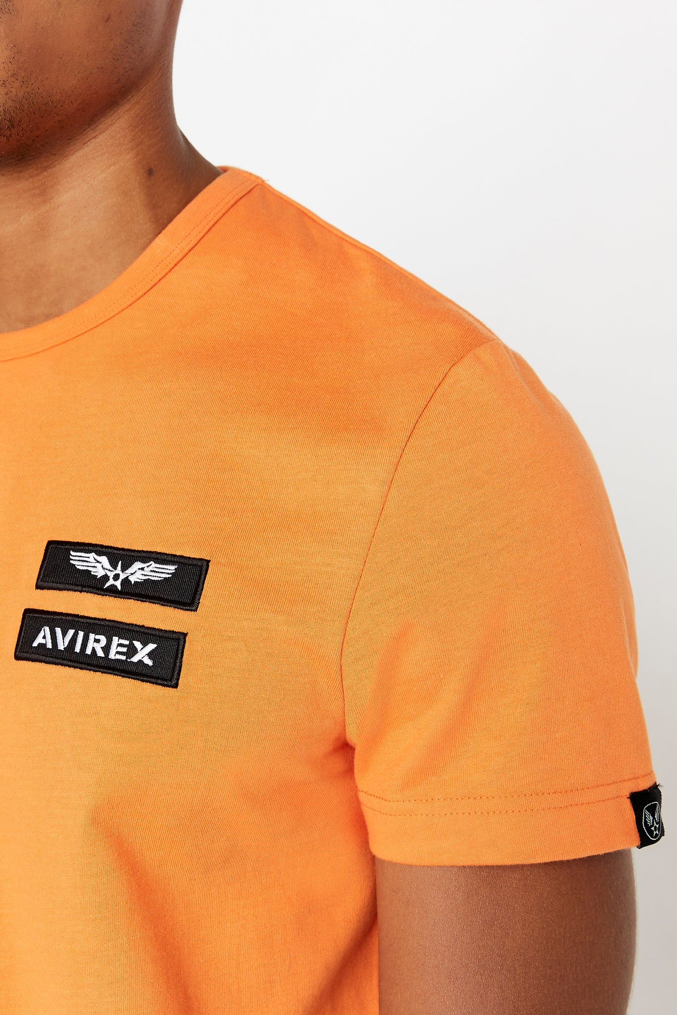 Detailed view of Avirex logo and letters patches on left chest and small logo tag on left sleeve