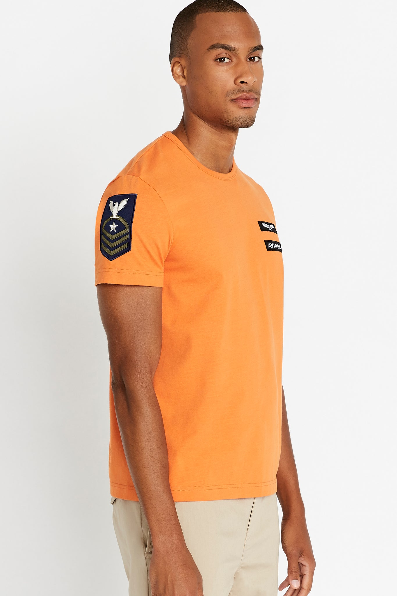 Side view of men wearing a light orange short sleeve crew T-shirt with a patch on right sleeve