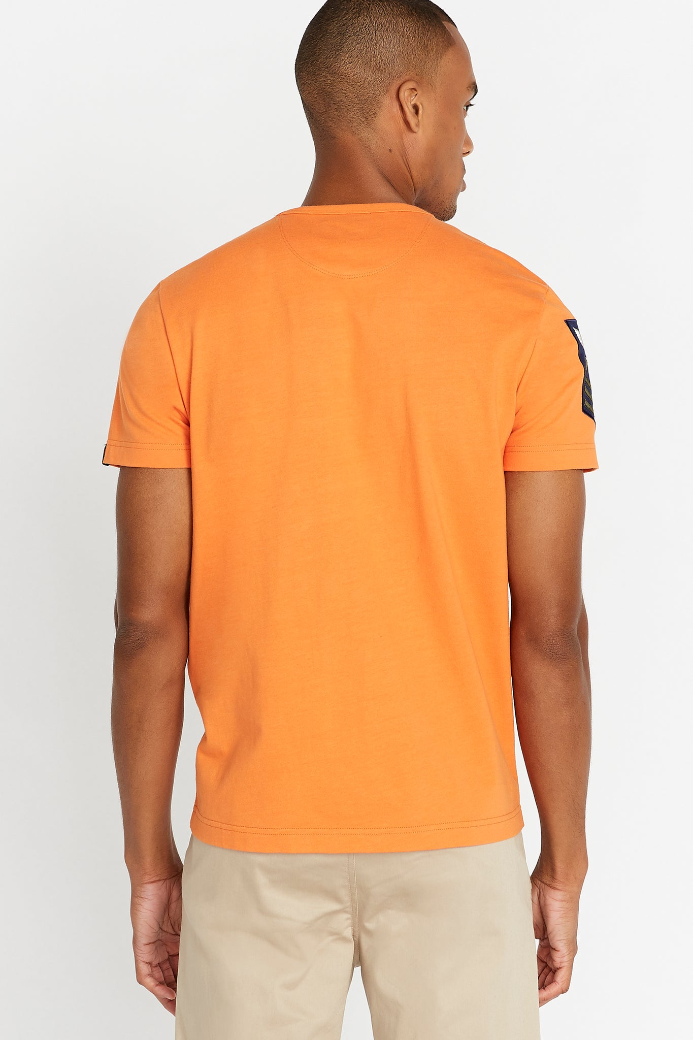 Back view of men wearing a light orange short sleeve crew T-shirt