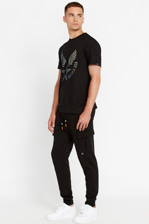 Side view of men wearing a black short sleeve crew T-shirt with front Avirex airforce wing-star print and black pants