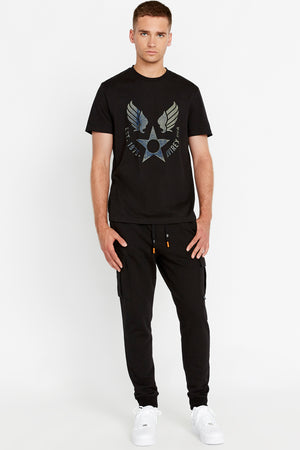 Full view of men wearing a black short sleeve crew T-shirt with front Avirex airforce wing-star print and black pants