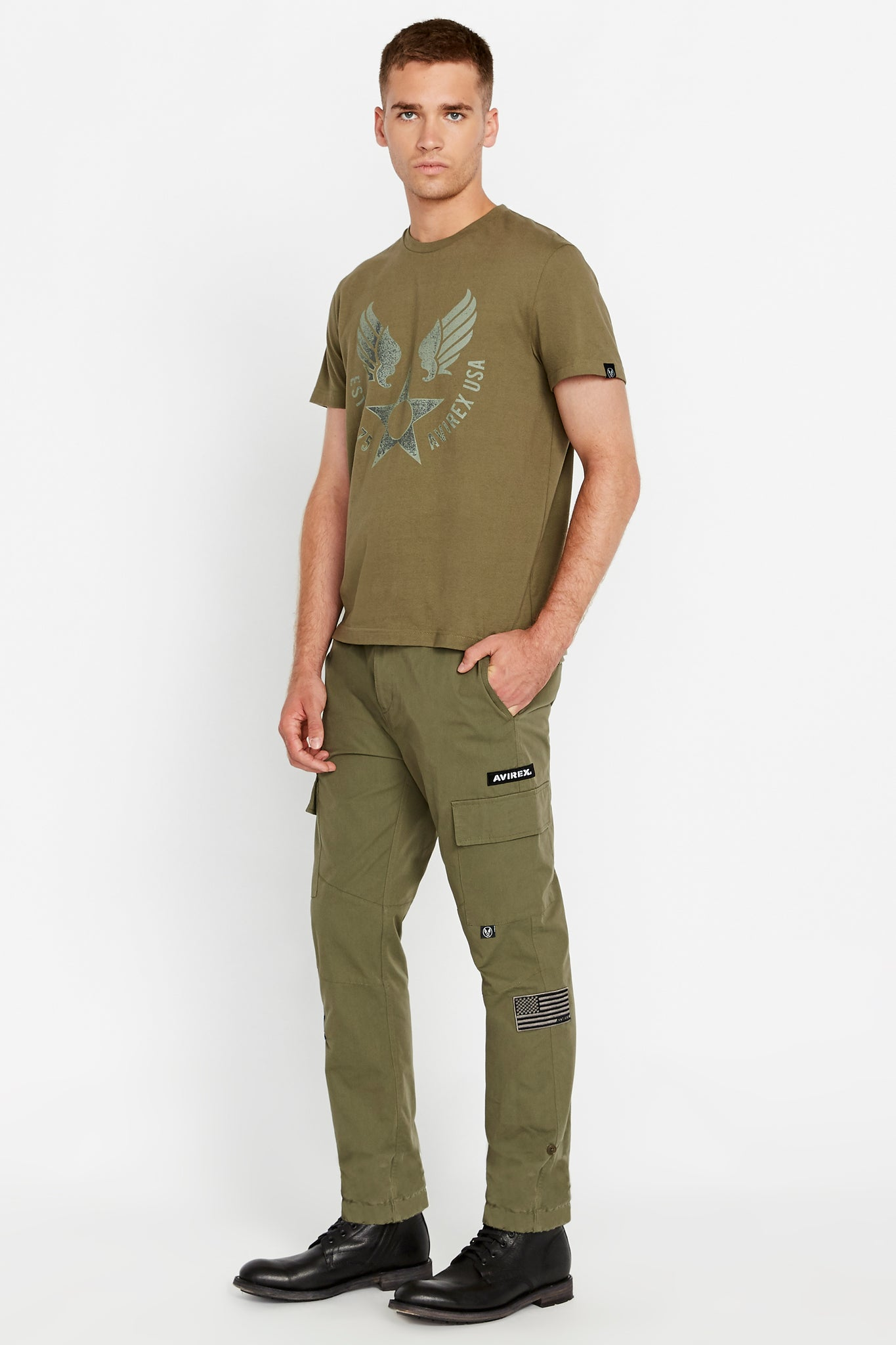 Side view of men wearing an olive short sleeve crew T-shirt with front Avirex airforce wing-star print and olive pants