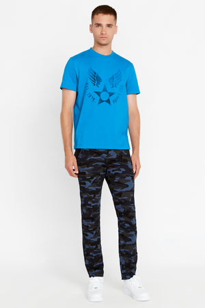 Full view of men wearing a royal blue short sleeve crew T-shirt with front Avirex airforce wing-star print and dark blue camo print pants
