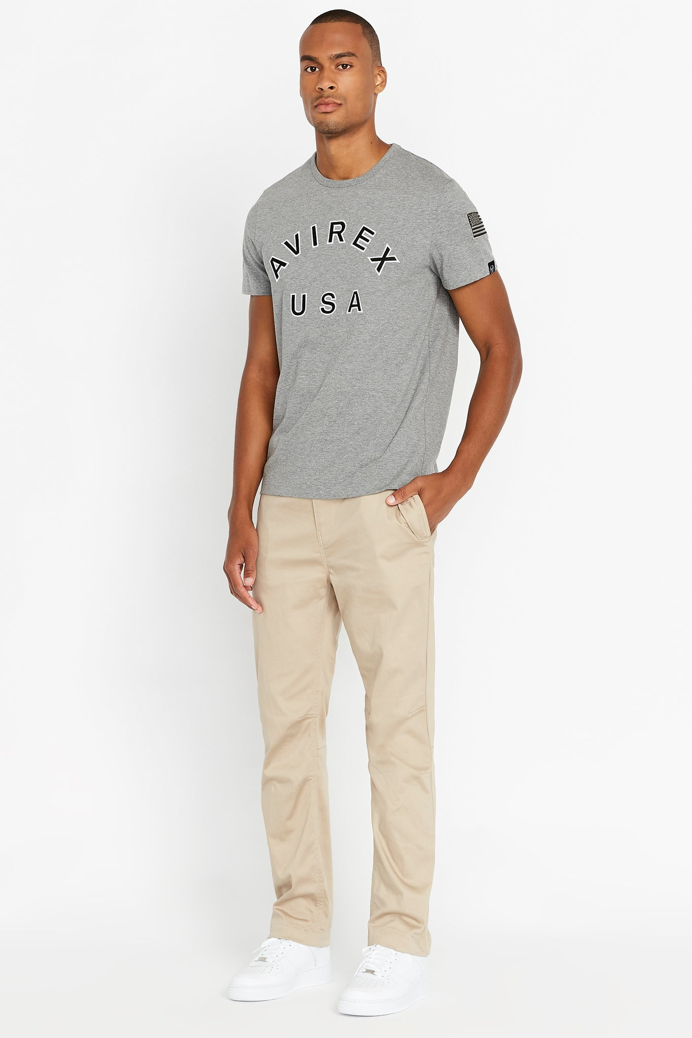Full view of men wearing a light grey short sleeve crew T-shirt with bold logo across the front saying Avirex USA and a patch on left sleeve and light beige pants