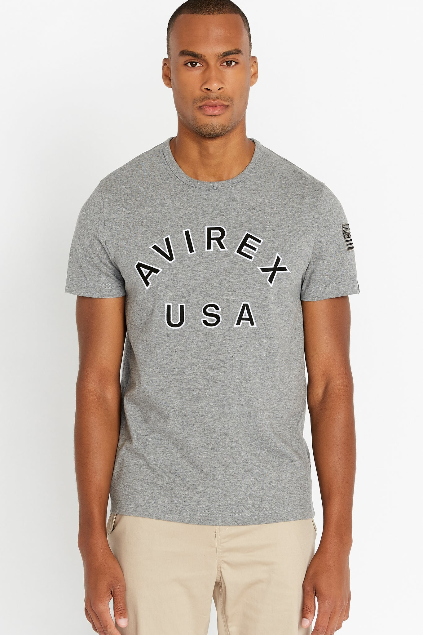Men wearing a light grey short sleeve crew T-shirt with bold logo across the front saying Avirex USA