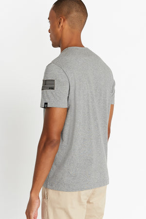 Back view of men wearing a light grey short sleeve crew T-shirt with patch on left sleeve