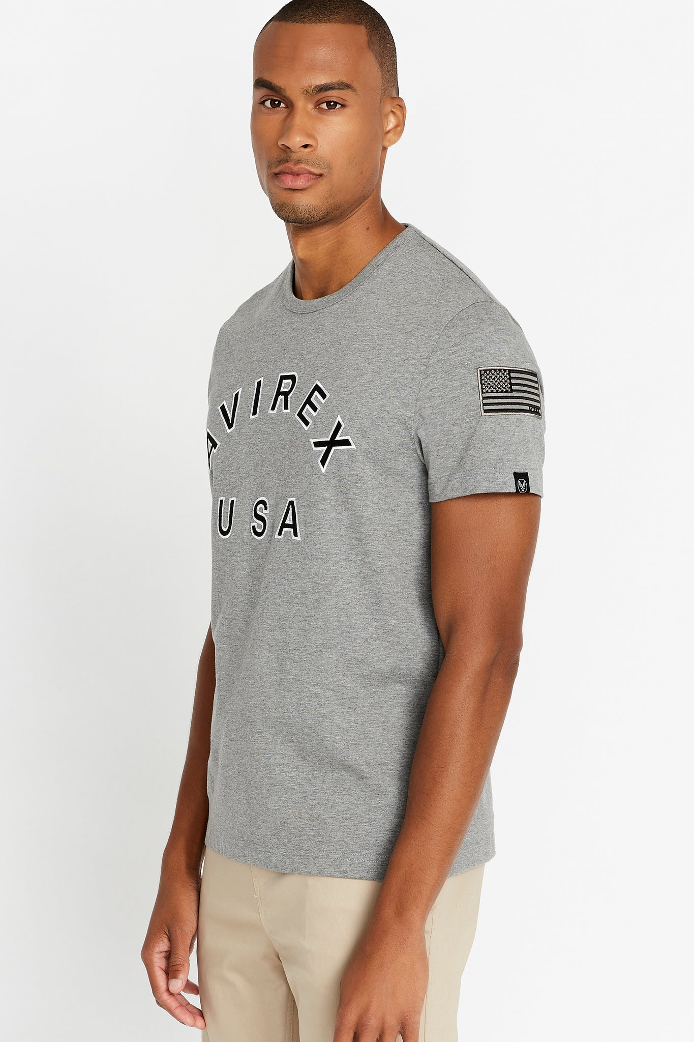 Side view of men wearing a light grey short sleeve crew T-shirt with bold logo across the front saying Avirex USA and a patch on left sleeve
